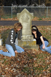 Two young women lying against a gravestone, sad